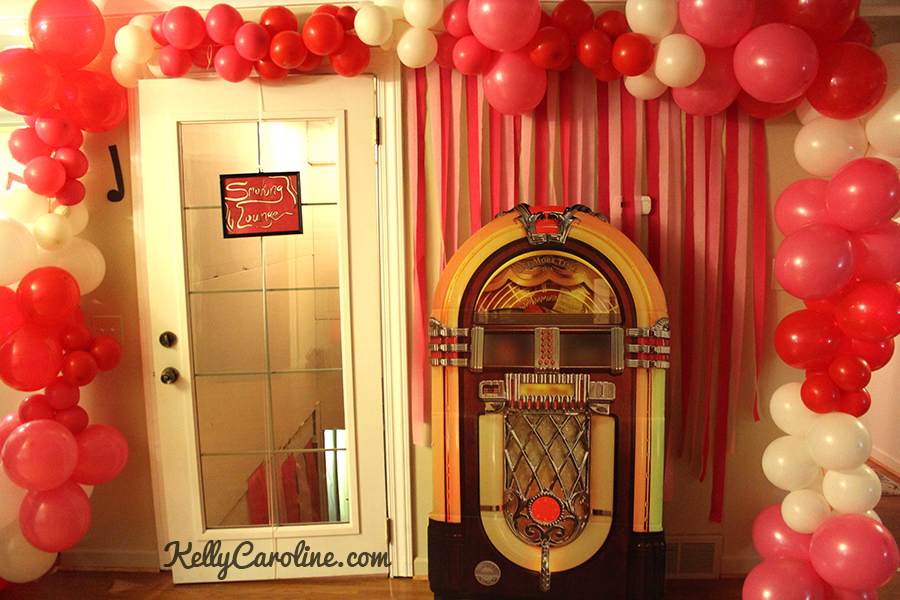 1950s party, decorations, decor, diy, balloon arch, pink and white balloons, jukebox, props, retro party, rockabilly, vintage, photo wall, party ideas