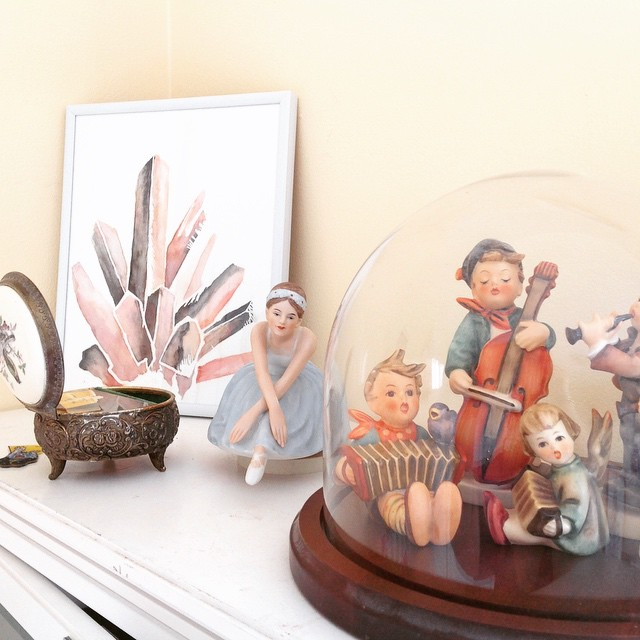 A little peek at my favorite shelf in my art room - my grandmother have me each of those Hummel figures, the musical ballerina and the jewelry box which is also a sweet little music box. I painted the crystal print in the background, inspired by a watercolor calendar I had several years ago. #hummels #hummel #holland #jewelry #watercolor #watercolors #jewelrybox #cello #violin #music #figures #ballerina #ballerina #ballet #glass #fragile #room #tour #craft #musical #musicians #roomtour #craftroom #art #heirloom #print #paper #pink #painting #paint #wood