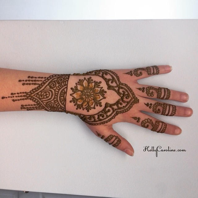 Henna design on the top of the hand with a floral mandala in the center. I loved the little rings on the fingers.